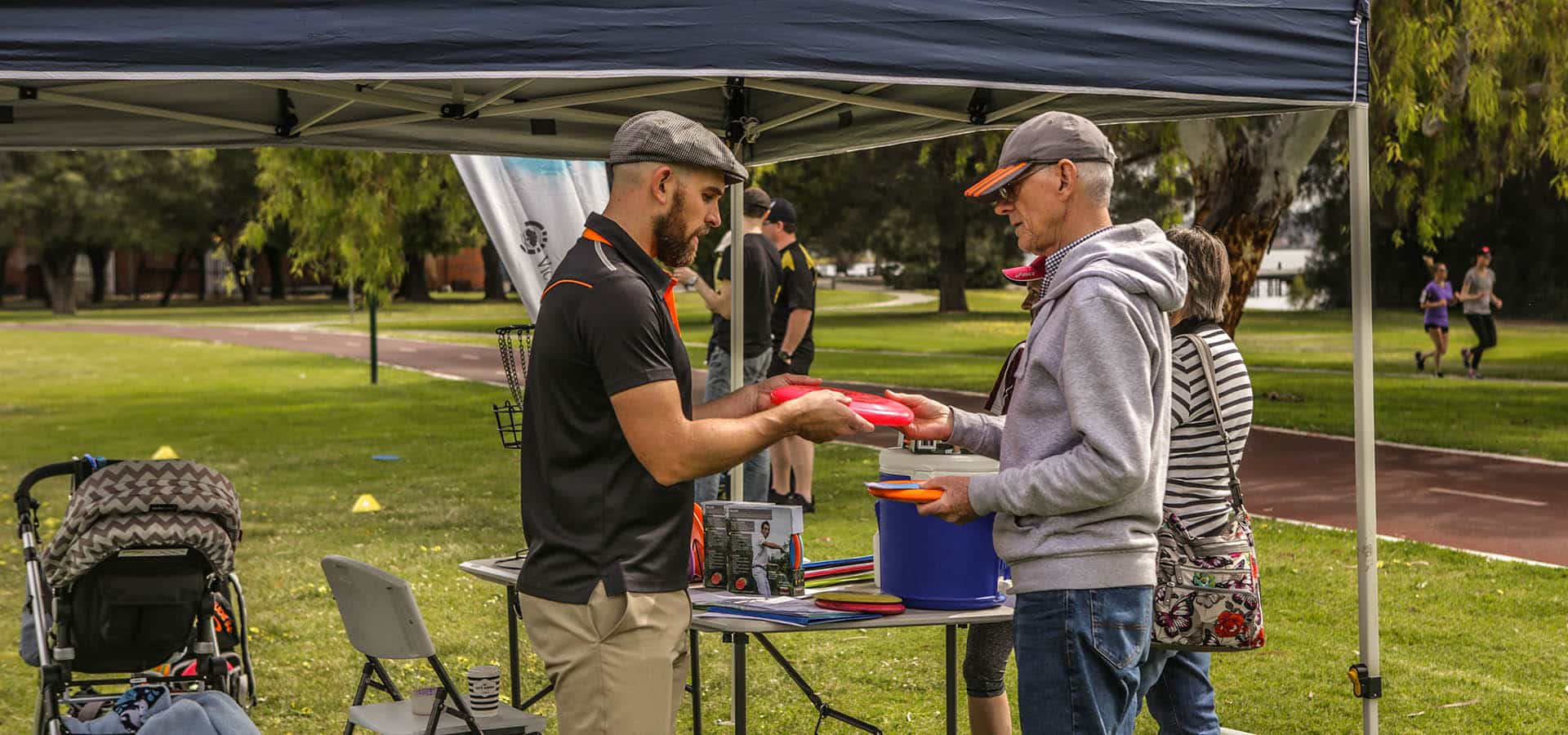 An image showing man people buying disc golf frisbee and two people running