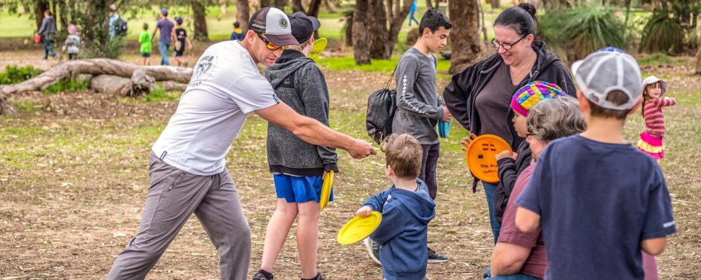 An image showing family playing disc golf frisbee at disc golf park