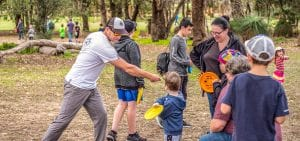 An image showing family playing disc golf frisbee in a park