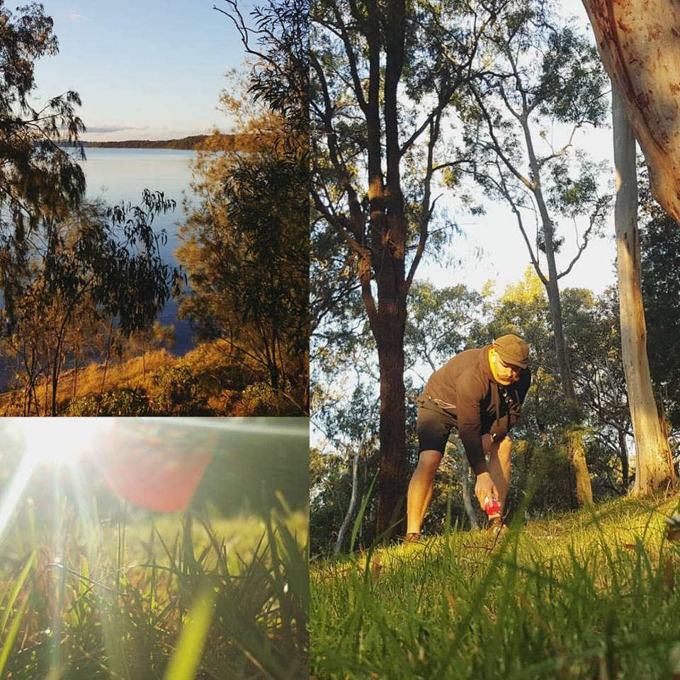 An image showing man playing disc golf frisbee in disc golf park that have beautiful lake