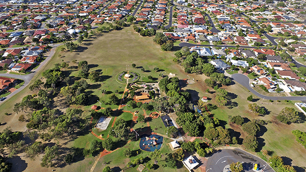 An image of a disc golf park surrounded by houses in a aerial mode shot