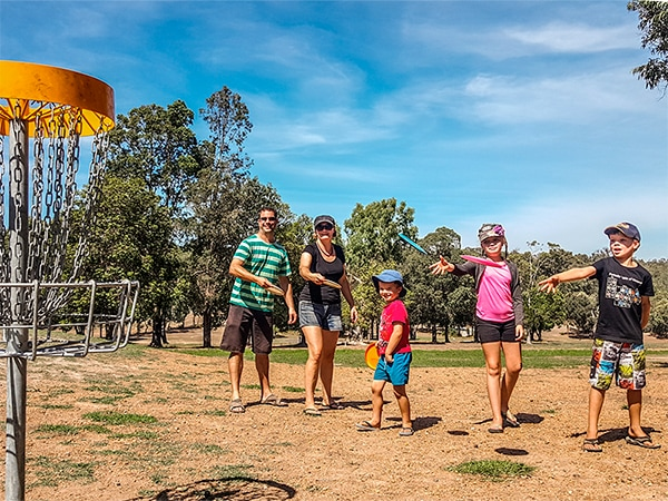 An image showing family playing disc golf frisbee