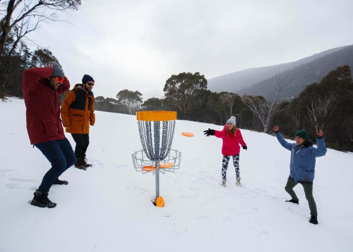 an image of 2 boys and 2 girls playing frisbee with a DIScatcher in the middle of snow