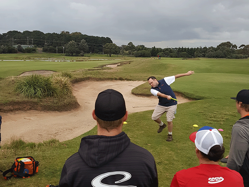 an image showing four men playing frisbee at the golf course