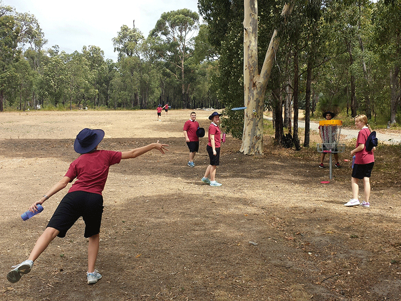 An image showing group of people in red playing disc golf frisbee