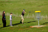 An image showing man playing disc golf frisbee with a kid and a woman