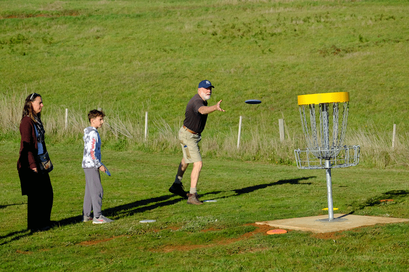 An image showing man playing disc golf frisbee with a kid and a woman by RAD Disk Golf Course Designers