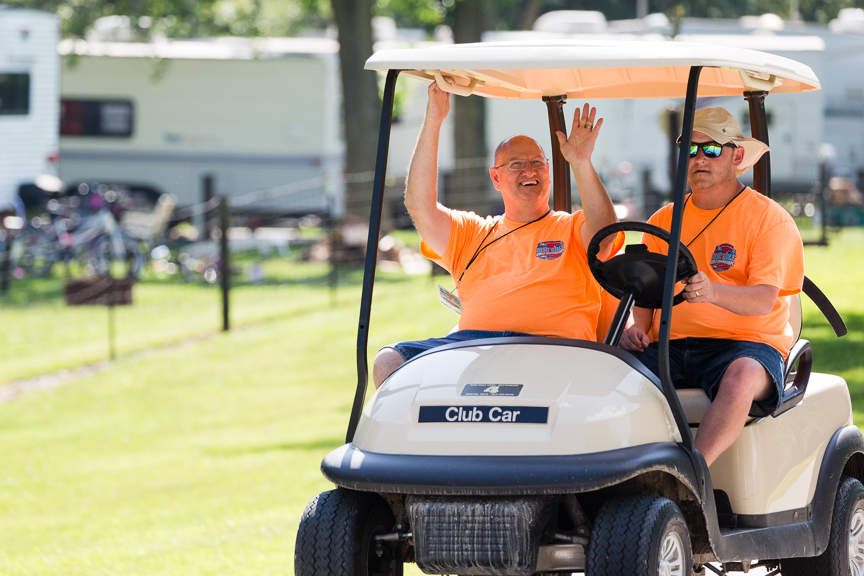 An image of two men riding a club car in a disc golf park