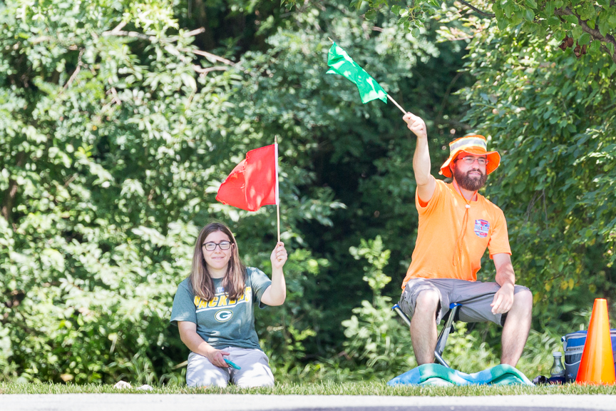 An image of a man and a woman sitting in a grass while waving a red and green flag