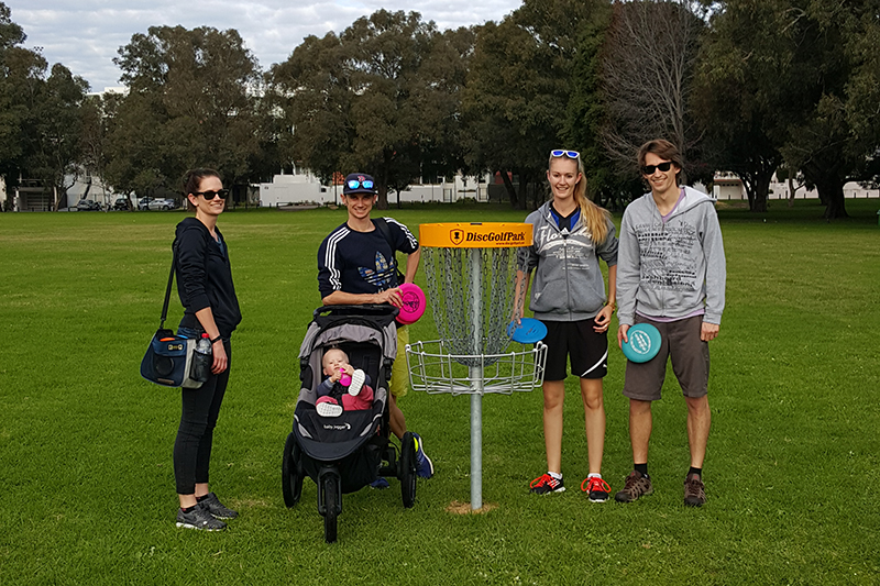 An image of a family on a disc golf course