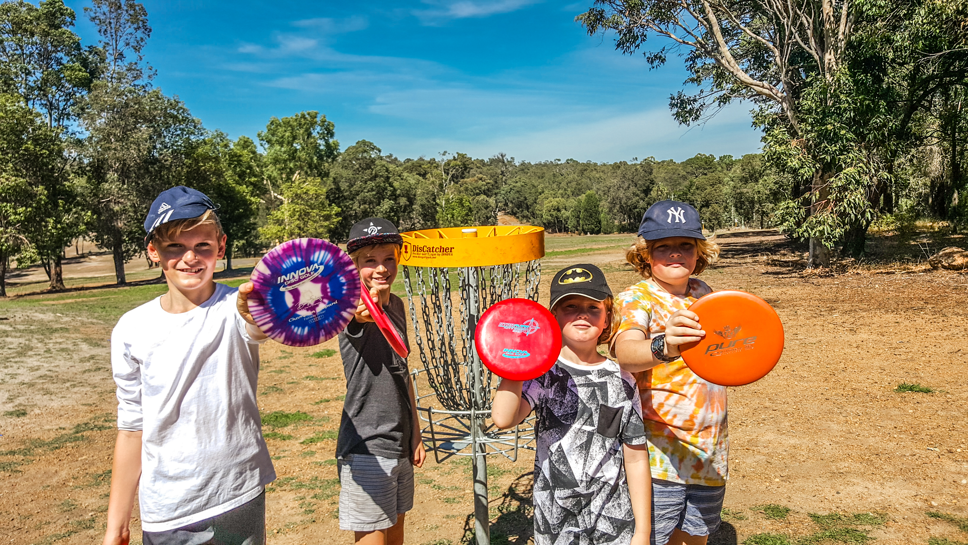 An image of group of boys holding frisbee in a disc golf park