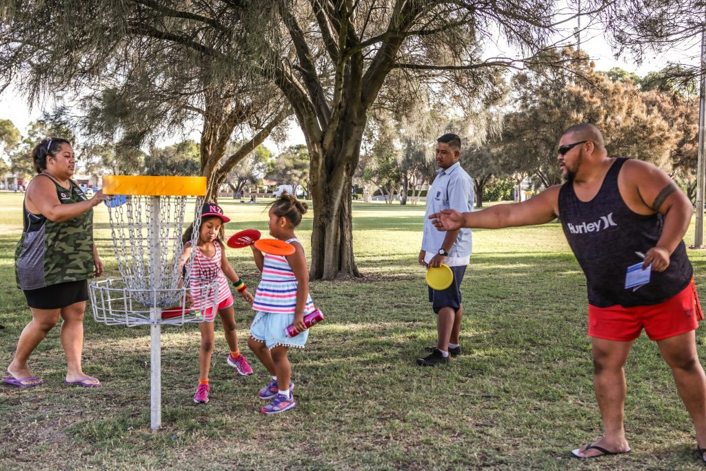 An image of family playing disc golf in a disc golf park