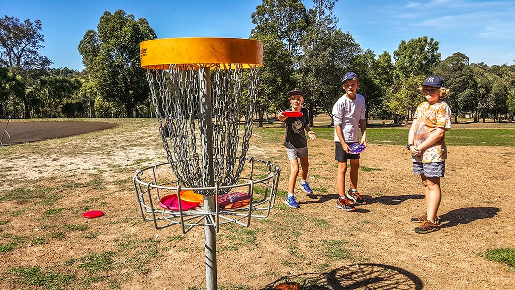 an image of kids playing disc golf