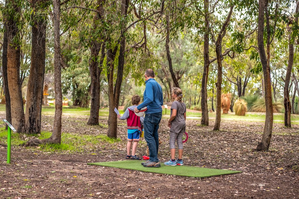 An image of family playing disc golf