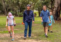 An image of men and kids walking in a disc golf park