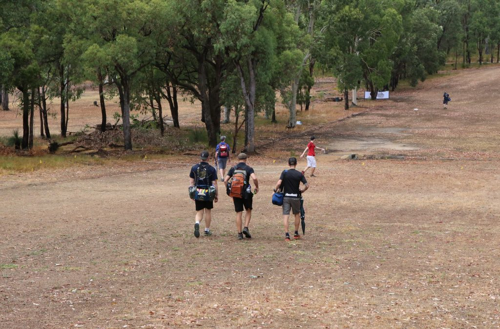 an image of group of people walking in a disc golf course