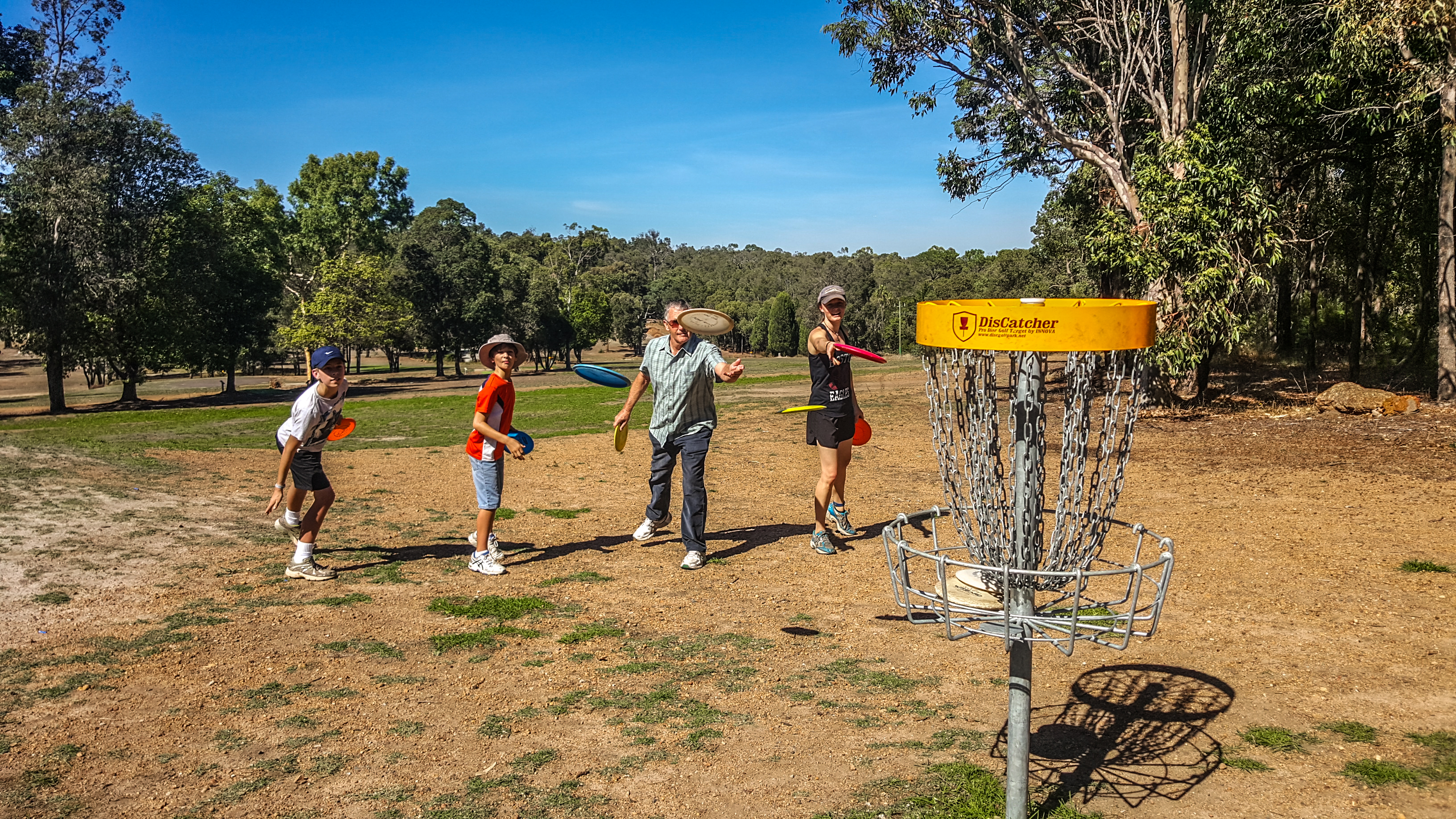 an image of people trying to shoot frisbee in a disc golf basket