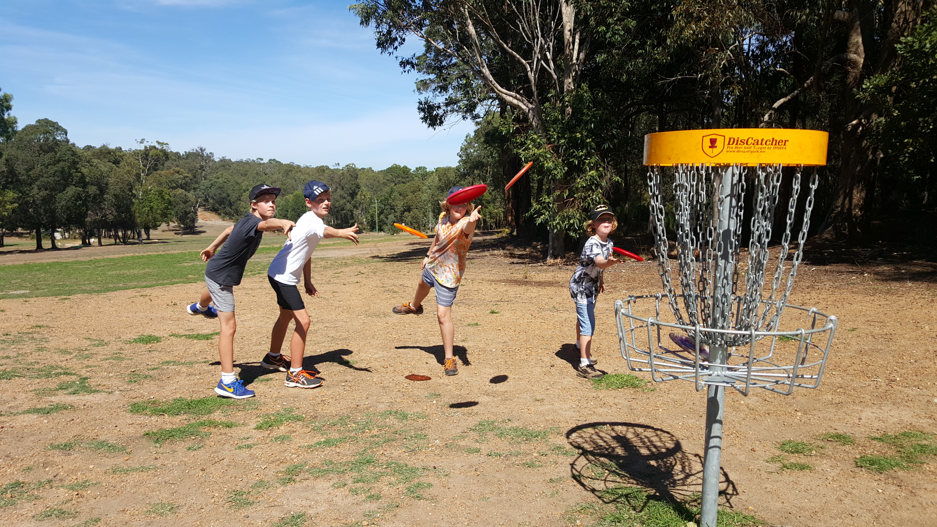an image of children playing disc golf in a disc golf park