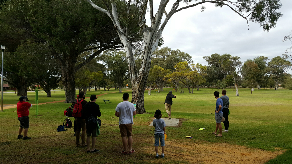 an image of group of men playing disc golf in disc golf park