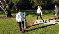 an image of three young women playing disc golf