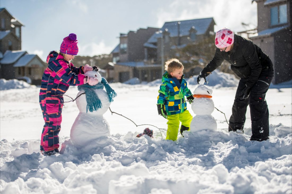 an image of kids playing and making snowman