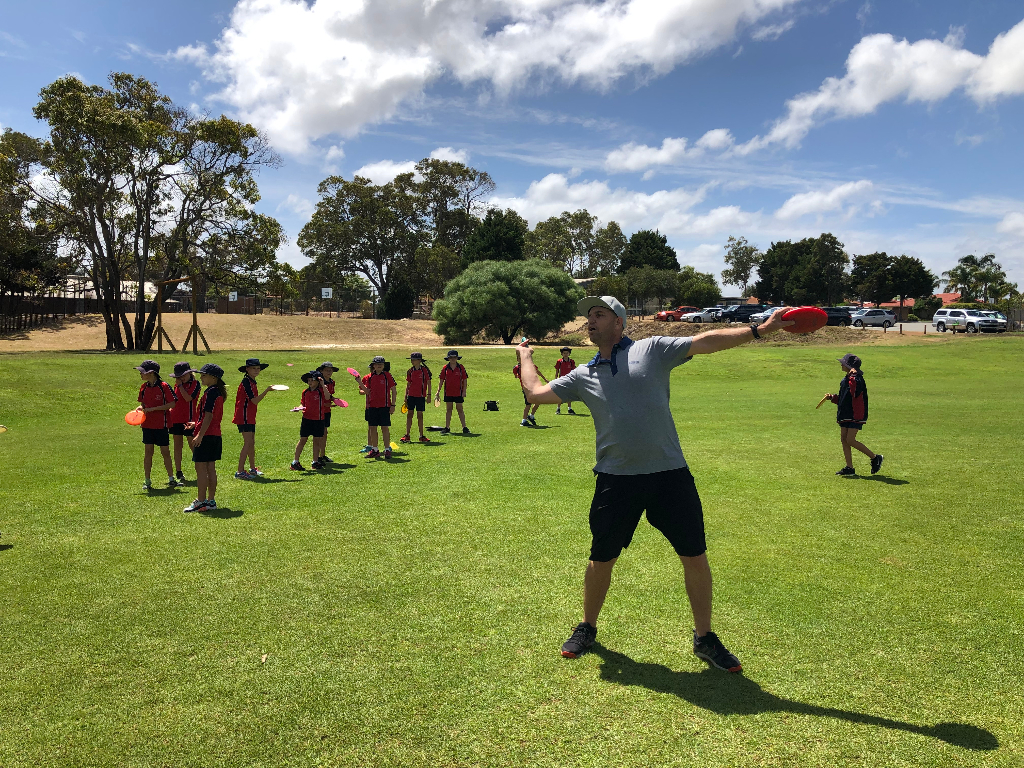 an image of group of kids under training of disc golf