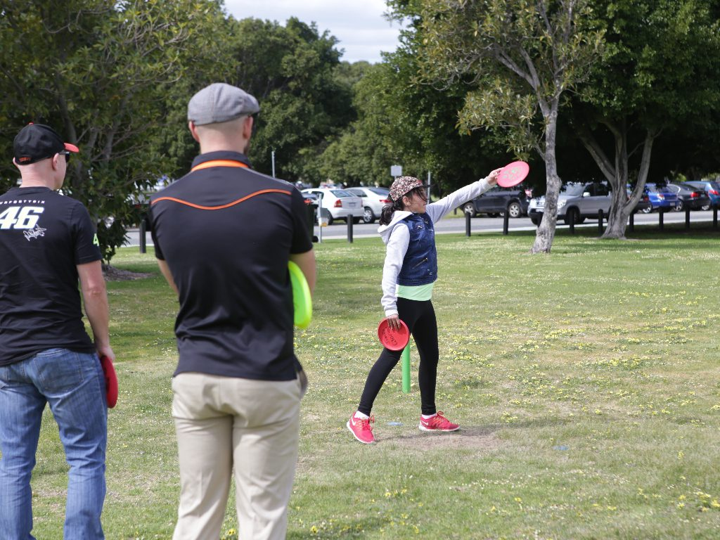 an image of woman playing disc golf while two men watching