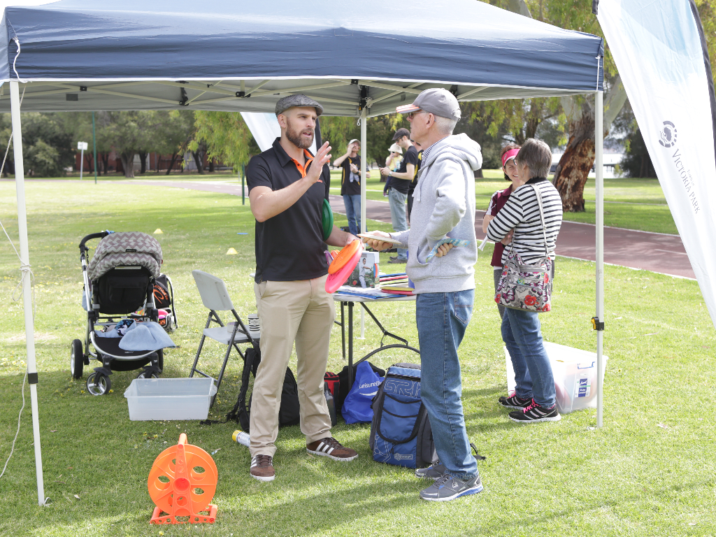 an image of two men talking in a disc golf park