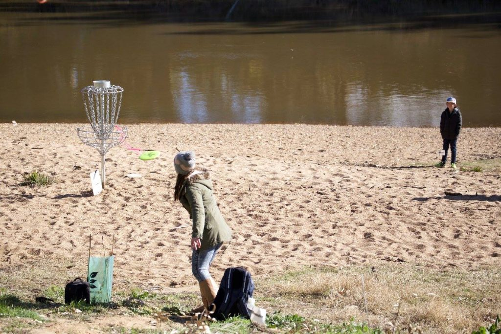 an image of a woman playing disc golf near the beach