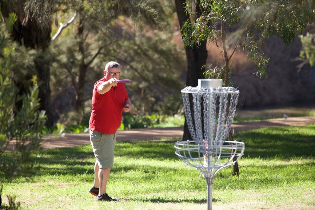an image of man trying to shoot a disc golf in a target
