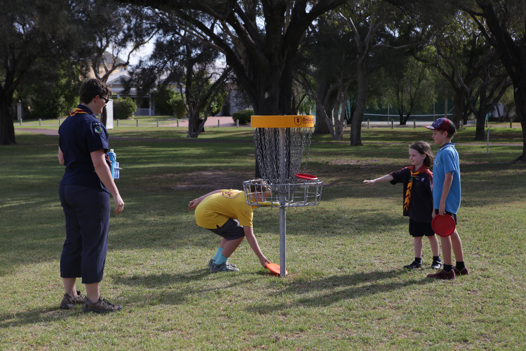 an image of kids and a lady playing disc golf