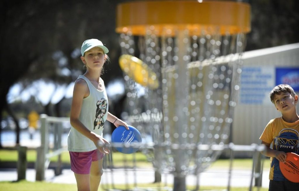 an image of a girl playing disc golf