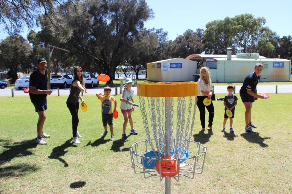 an image of kids and adults playing disc golf