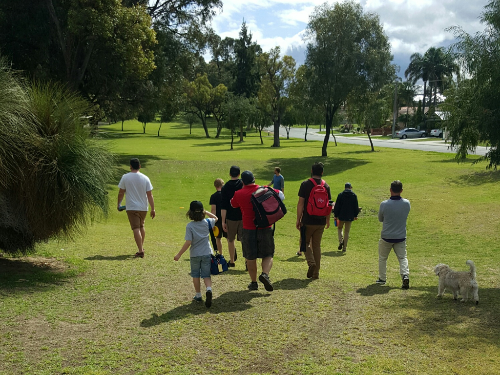 an image of kids walking at the disc golf course